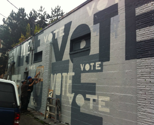 Men spray-painting 'Vote' on the side of a building