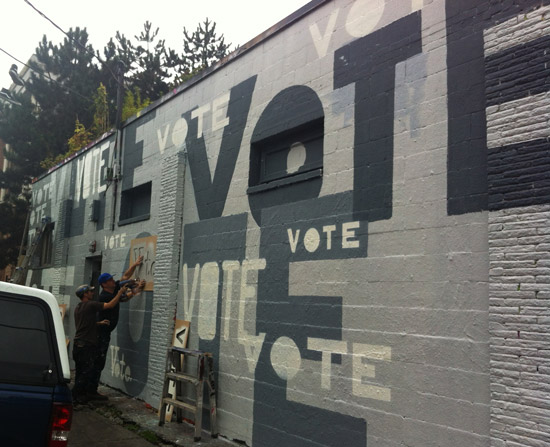 Men spray-painting Vote all over wall